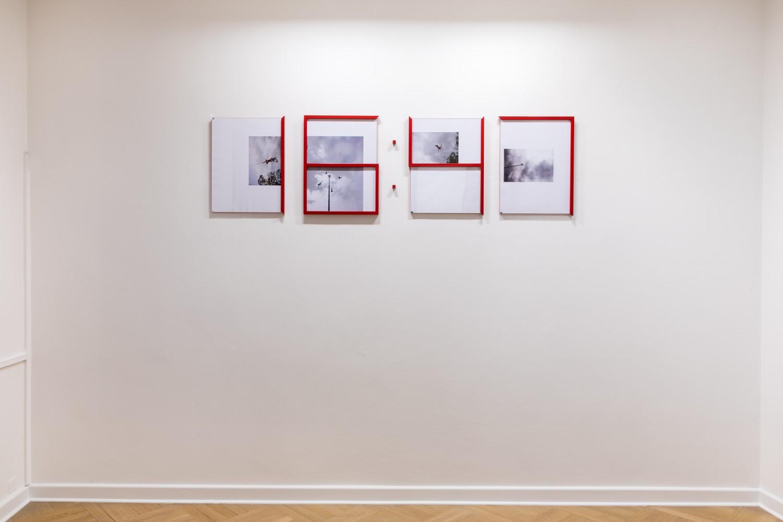 """Die aus mehreren Elementen bestehende Installation """"Sistemo en tiempo real"""" der Künstlerin Adriana Lara ist eine vierteilige Collagenserie, deren Rahmung das Bildmotiv so durchkreuzt, dass eine Zeitangabe visualiert wird. Der Faktor Zeit als Maßstab von Produktivität wird in dieser Arbeit erfahrbar, indem die vier Collagen über die Dauer der Ausstellung ihre Position wechseln und so immer wieder veränderte Zeitpunkte manifestieren."""
