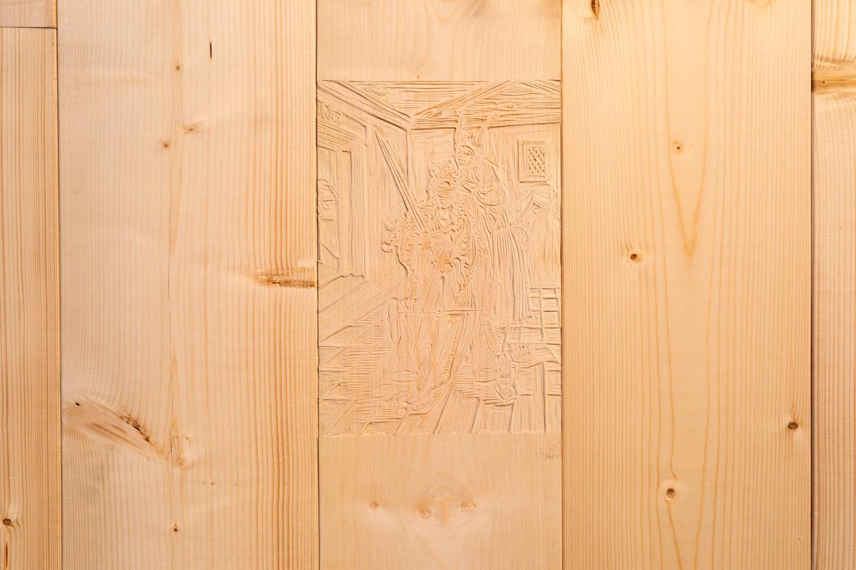"""Die Arbeit mit dem Titel """"Narrenschiff"""" von Tyler Coburn ist eine Wandinstallation, die die vorherrschende Architektur der Ausstellungsräume durchbricht und in ein Spiel mit Vorder- und Rückseitigkeit eintritt. So zeigt sich erst auf den zweiten Blick ein in die WAnd integrierter Holzschnitt, der das Verhüllen der Augen der Göttin der Gerechtigkeit, Justitia, durch einen Narren zeigt. Es ist die Reproduktion eines Holzschnitts, der mutmaßlich von Albrecht Dürer gefertigt wurde und in dem erstmals 1494 von Sebastian Brant veröffentlichten Buch Narrenschiff als Illustration erscheint. Erst seit dem 16. Jahrhundert wird die Blindheit Justitia als Symbol für Neutralität wahrgenommen. Diese Darstellung, der ersten bekannten Darstellung von Justitia überhaupt, zeigt die Göttin der Gerechtigkeit geblendet von Spott und der Korruption des Gesetzes."""