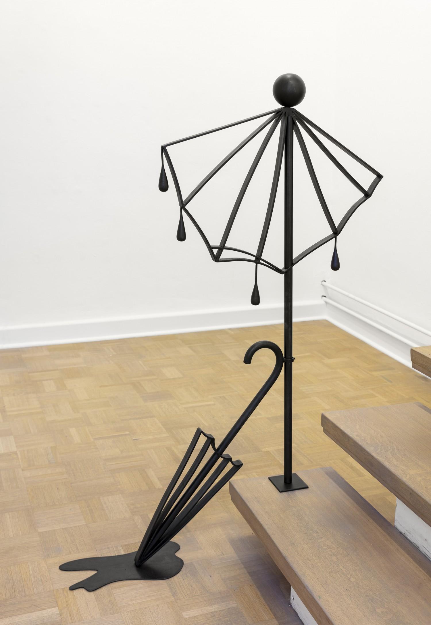 """Ein Objekt der vierteiligen Werkreihe """"Ballustrade"""" von Julie Béna aus dem Jahr 2020, das aus schwarz beschichtetem Stahl besteht und auf der letzten Treppenstufe platziert ist. Den Objekten kommt Autonomie und Funktion gleichermaßen zu, sie sind Bild und tatsächlich Balustrade zugleich."""