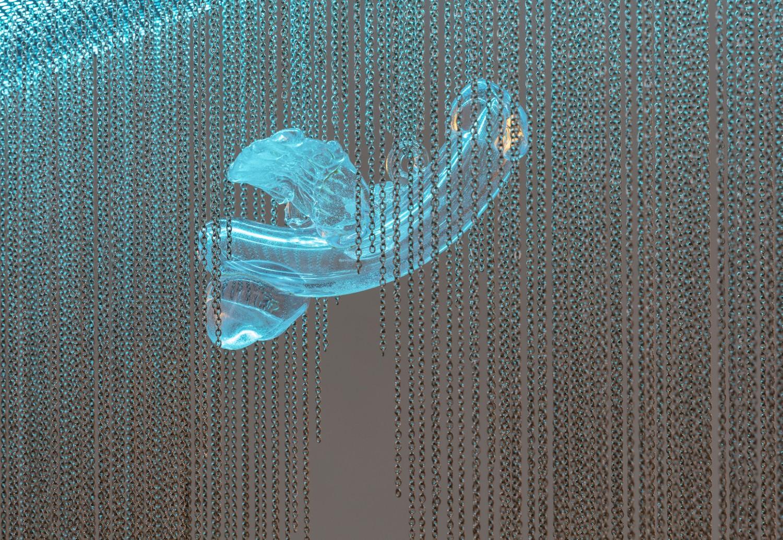 """Das Objekt """"Rise"""" von Julie Béna zeigt sich als ein wellenförmiger Kronleuchter, zwischen dessen Edelstahlketten drei übergroße, mundgeblasene geflügelte Phalli aus Glas zum Vorschein kommen. Die Arbeit stellt vorherrschende Genderkategorien infrage, indem sie die Konnotationen des Phallussymbols verunsichern."""