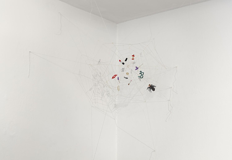"""Die autobiographische Arbeit """"Spider Net 33"""" von Julie Béna besteht aus handgeklöppelter Spitze in Form eines Spinnennetzes, das in einer Ecke unter der Decke gespannt ist. In dem Spinnennetz sind Motive wie ein Lippenstift, eine Haarnadel, eine Zigarette, ein goldenes Armband, ein Kussmund oder ein geflügelter Phallus zu erkennen."""