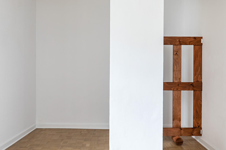 Beim Durchschreiten der Ausstellungsräume begegnen einem weitere Holzgestellt. Auf dieser Abbildung ist ein zweiseitiges, braunes Gatter auf Walzen zu sehen, welches sich hinter einer Säule versteckt.