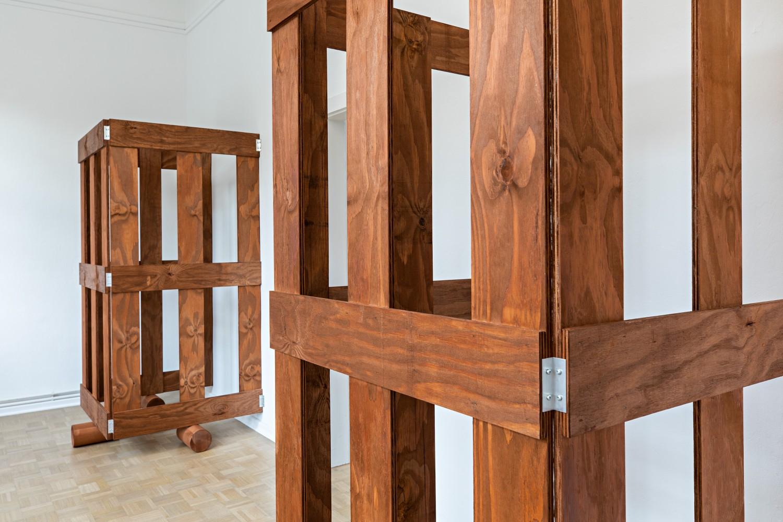 Die zwei dreiseitigen Holzgatter auf Walzen im kleinen Kabinettraum wirken viel massiver als die selben Gatter in den größeren ansonsten leeren Ausstellungsräumen. Die Nahaufnahme zeigt, dass der Künstler die Schaniere, welche die Gatter zusammenhalten, außen angebracht hat, und sie somit für die Betrachter*innen sichtbar sind.