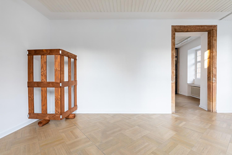 Zurück zum ersten Objekt: die rasterartige Anordnung der Holzgatter wird nun deutlich. Auch wenn man das Objekt im anderen Raum durch die Wand hindurch nicht sehen kann, lässt sich nun imaginieren wie das Gatter sich über Wände hinweg fortsetzt und so eigene Räume schafft.